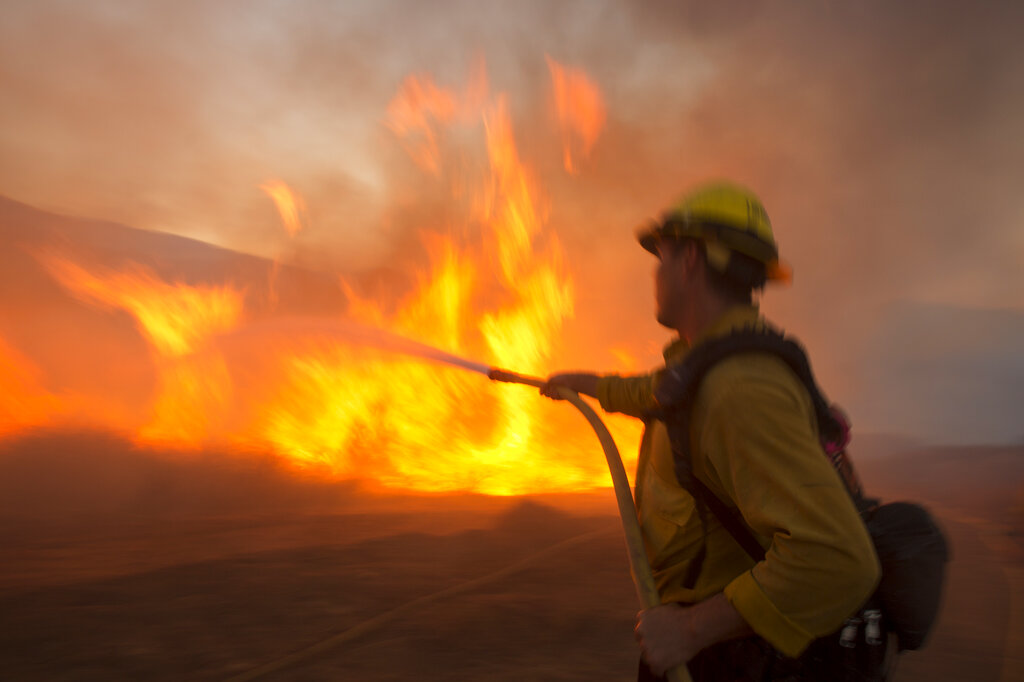 A firefighter battles the Apple Fire in Banning, Calif., Saturday, Aug. 1, 2020. (AP Photo/Ringo H.W. Chiu)