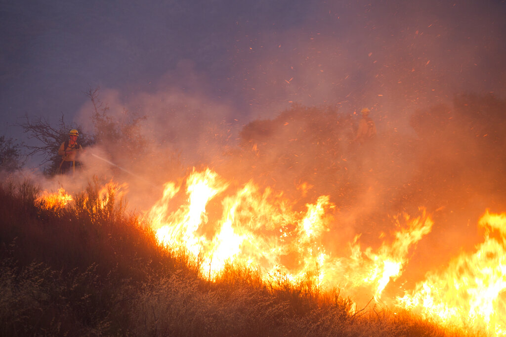 Firefighters battle the Apple Fire in Banning, Calif., Saturday, Aug. 1, 2020. (AP Photo/Ringo H.W. Chiu)