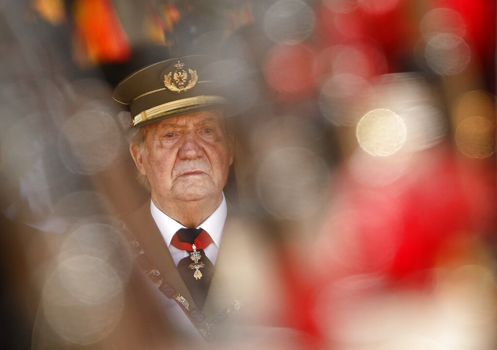 FILE - In this June 3, 2014 file photo then King Juan Carlos attends a military ceremony in San Lorenzo de El Escorial, outside Madrid, Spain. The royal family's website on Monday Aug. 3, 2020, published a letter from Spain's former monarch, King Juan Carlos I, saying he is leaving Spain to live in another country, amidst a financial scandal. (AP Photo/Daniel Ochoa de Olza, File)