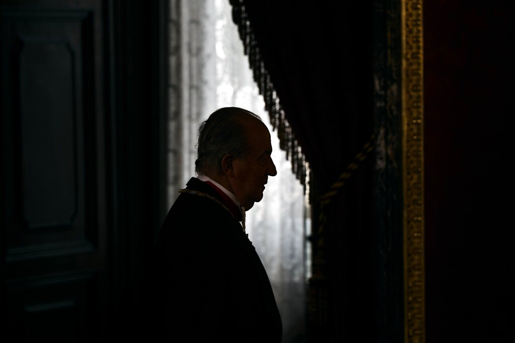 FILE - In this June 9, 2014 file photo then Spanish King Juan Carlos enters the room during a welcome ceremony before a gala dinner for Mexico's President Enrique Pena Nieto, at the Royal Palace, near Madrid. The royal family's website on Monday Aug. 3, 2020, published a letter from Spain's former monarch, King Juan Carlos I, saying he is leaving Spain to live in another country, amidst a financial scandal. (AP Photo/Daniel Ochoa de Olza, File)