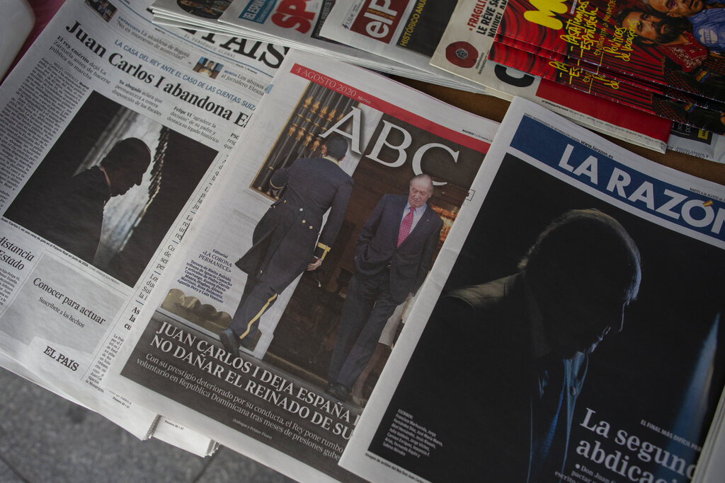 Front pages of newspapers are displayed with the news on Spain's former monarch, King Juan Carlos I, in Madrid, Spain, Tuesday, Aug. 4, 2020. Speculation over the whereabouts of former monarch Juan Carlos is gripping Spain, a day after he announced he was leaving the country for an unspecified destination amid a growing financial scandal. (AP Photo/Manu Fernandez)