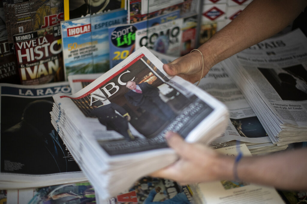 Front pages of newspapers are displayed with the news of Spain's former monarch, King Juan Carlos I in Madrid, Spain, Tuesday, Aug. 4, 2020. Speculation over the whereabouts of the former monarch is gripping Spain, a day after he announced he was leaving the country for an unspecified destination amid a growing financial scandal. (AP Photo/Manu Fernandez)