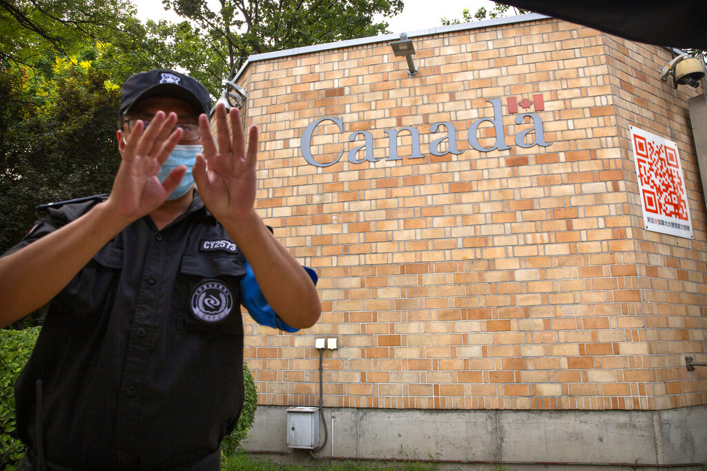 A security officer wearing a face mask to help protect against the coronavirus gestures outside the Canadian Embassy in Beijing, Thursday, Aug. 6, 2020. China has sentenced a Canadian citizen to death on charges of manufacturing the drug ketamine amid heightened tension between the two countries. (AP Photo/Mark Schiefelbein)