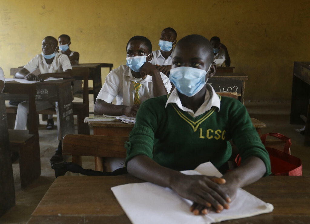 """File---File picture taken Aug.4, 2020 shows students from Lagos State Model School wearing face mask to protect against coronavirus attend lectures inside a class room in Lagos, Nigeria. Nigeria officials resumed both public and private schools on Monday for students following months of closure to curb the spread of coronavirus. As Germany's 16 states start sending millions of children back to school in the middle of the global coronavirus pandemic, those used to the country's famous """"Ordnung"""" are instead looking at uncertainty, with a hodgepodge of regional regulations that officials acknowledge may or may not work. (AP Photo/Sunday Alamba, File)"""
