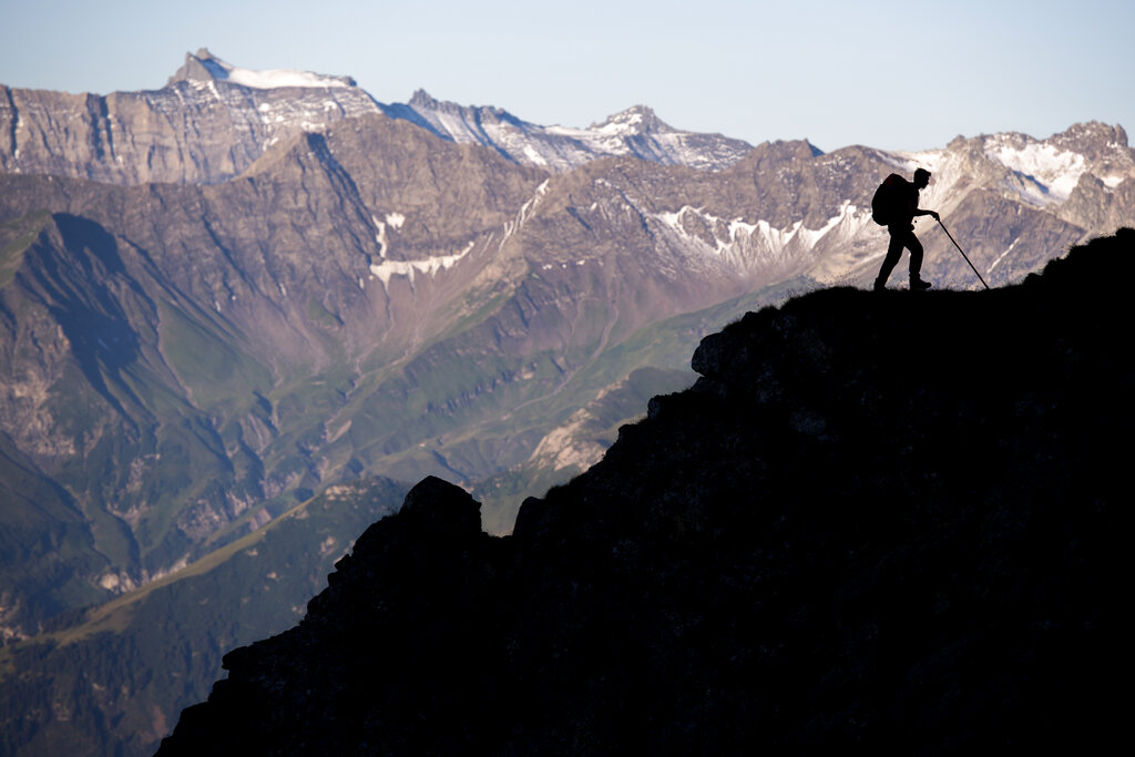 A sheperd is on his way as a flock of sheep is crossing alpine terrain on Friday, August 7, 2020, under the