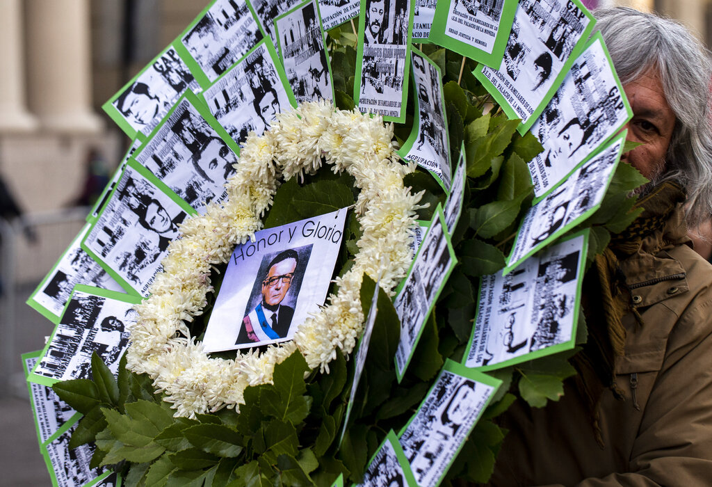 A supporter of the Chile's late President Salvador Allende holds a flower arrangement that will be placed outside the eastern entrance of La Moneda presidential palace on the anniversary of the 1973 military coup and subsequent death of Allende, in Santiago, Chile, Wednesday, Sept. 11, 2019. It was through the eastern entrance that Allende's body was carried by soldiers and firefighters from the destroyed presidential palace 46 year ago during the coup that ousted the democratically elected leader and began the 17-year dictatorship of Gen. Augusto Pinochet. The arrangement is adorned with photos of the victims of the dictatorship as well as a sign on the center with a photo of Allende and text that reads in Spanish