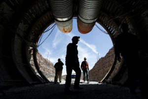 FILE - In this April 9, 2015, file photo, people walk into the south portal of Yucca Mountain during a congressional tour of the proposed radioactive waste dump near Mercury, Nev., 90 miles northwest of Las Vegas. The Trump administration's proposed budget for the U.S. Energy Department drew criticism Tuesday, March 3, 2020, as Democratic senators voiced concerns that spending to clean up sites contaminated by decades of nuclear research and bomb-making was being cut in order to fund modernization of the nation's nuclear arsenal. (AP Photo/John Locher, File)