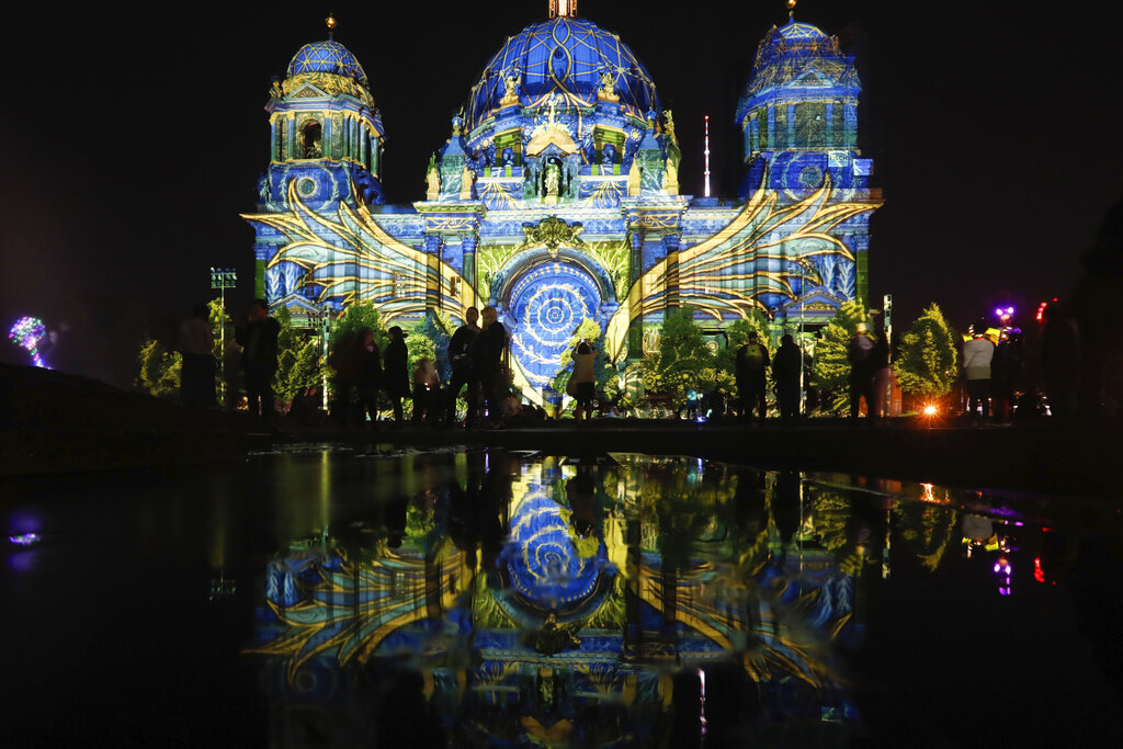 The Berlin Cathedral is illuminated during the 'Festival of Lights' event in Berlin, Germany, Friday, Sept. 11, 2020. Berlin's most famous landmarks and buildings will be glowing and sparkling with various colours and types of light and projections during the festival, which runs from Friday Sept. 11 until Sunday, Sept. 20, 2020, at the German capital. (AP Photo/Markus Schreiber)
