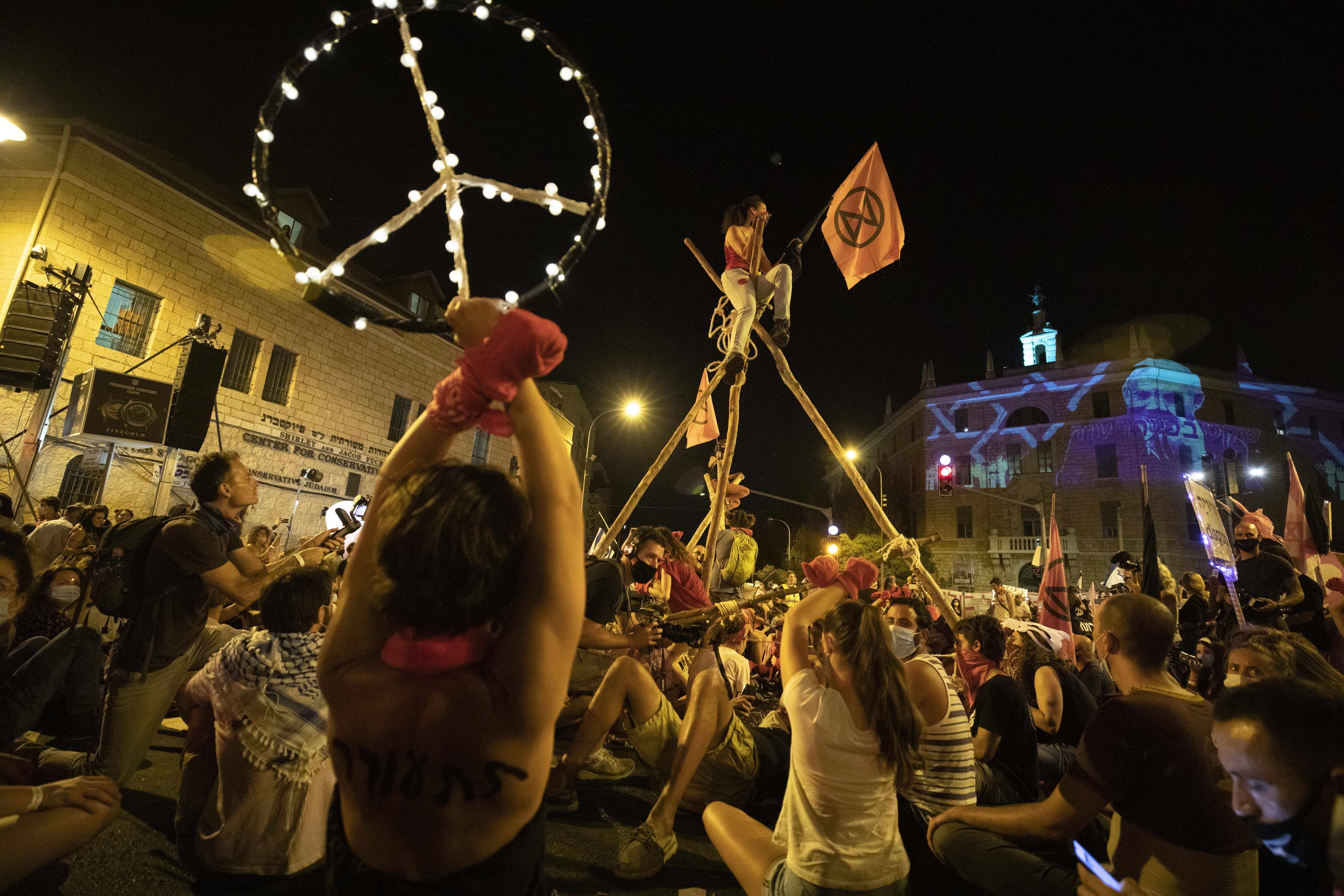 Protesters gather for a demonstration against Prime Minister Benjamin Netanyahu outside his official residence in Jerusalem, Saturday, Sept. 12, 2020, demanding he resign over his trial on corruption charges and what is widely seen as his mishandling of the coronavirus pandemic. (AP Photo/Sebastian Scheiner)