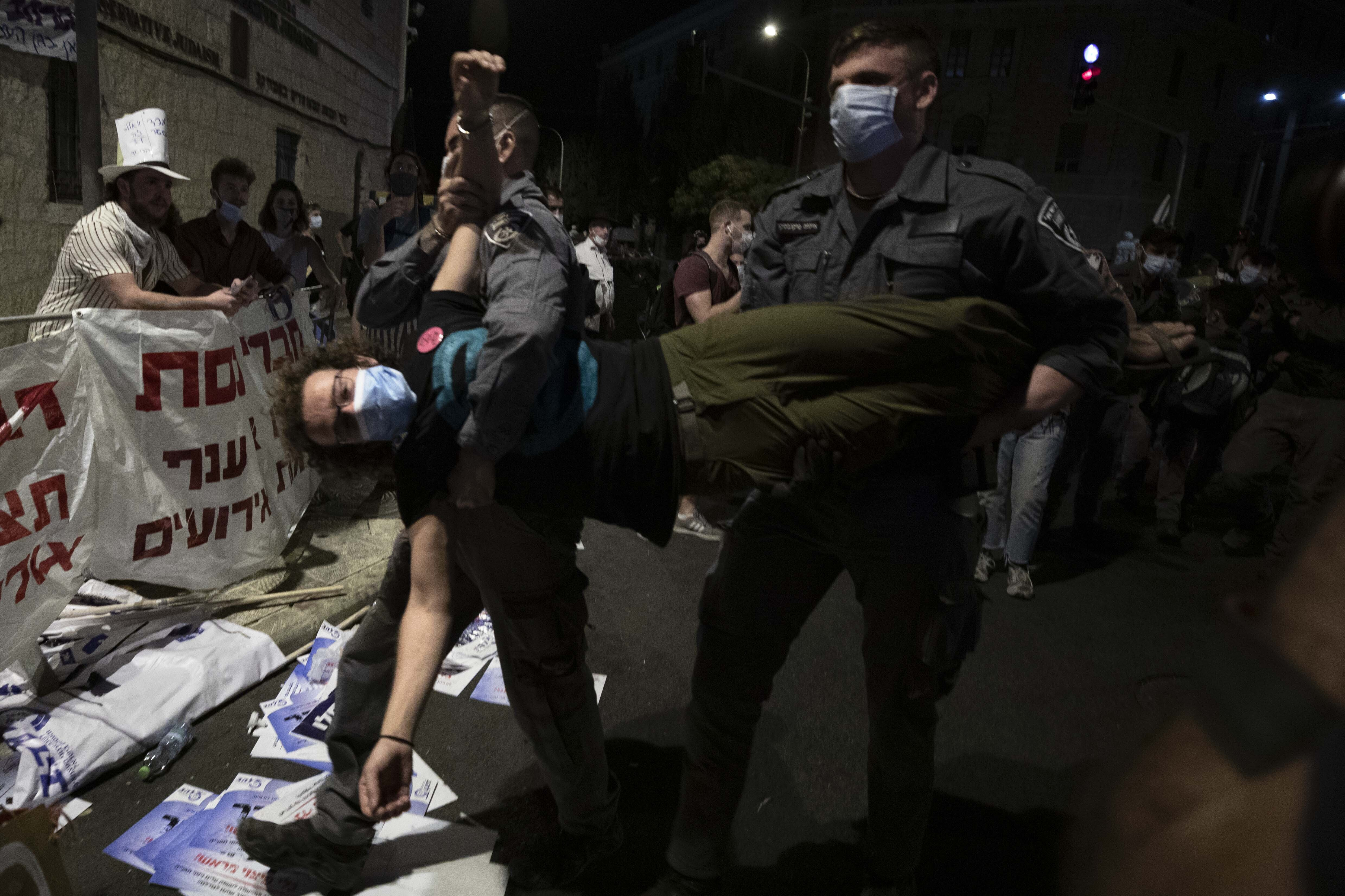 Police officers detain a protester during a demonstration against Prime Minister Benjamin Netanyahu outside his official residence in Jerusalem, Saturday, Sept. 12, 2020, demanding he resign over his trial on corruption charges and what is widely seen as his mishandling of the coronavirus pandemic. (AP Photo/Sebastian Scheiner)