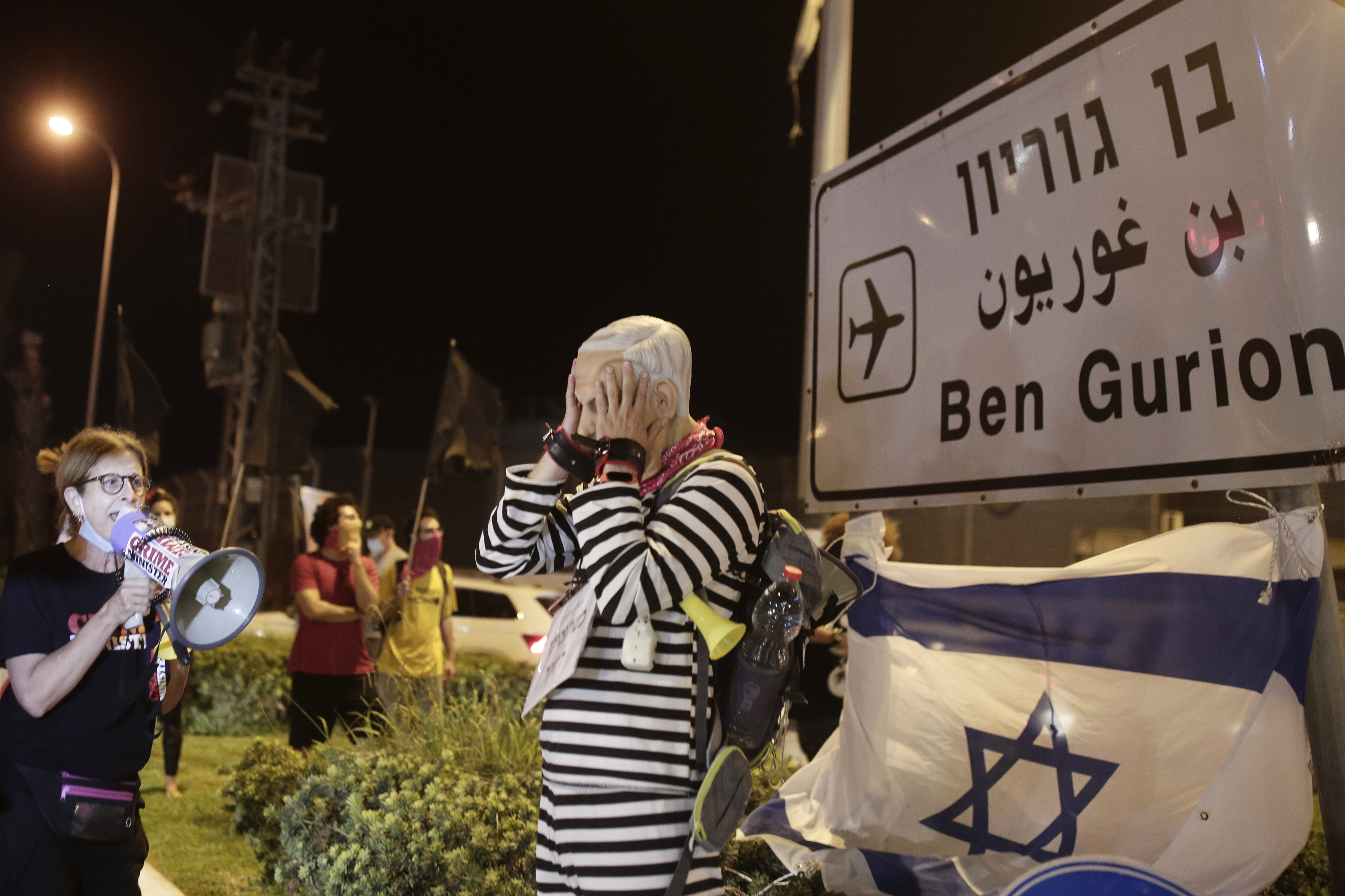 A protester wearing a rubber mask representing Israeli Prime Minister Benjamin Netanyahu stands at an entrance to Ben Gurion Airport, where Netanyahu and his family were expected to fly with an Israeli delegation to the U.S. for a ceremony with the United Arab Emirates, in Tel Aviv, Sunday, Sept. 13, 2020. (AP Photo/Maya Alleruzzo)