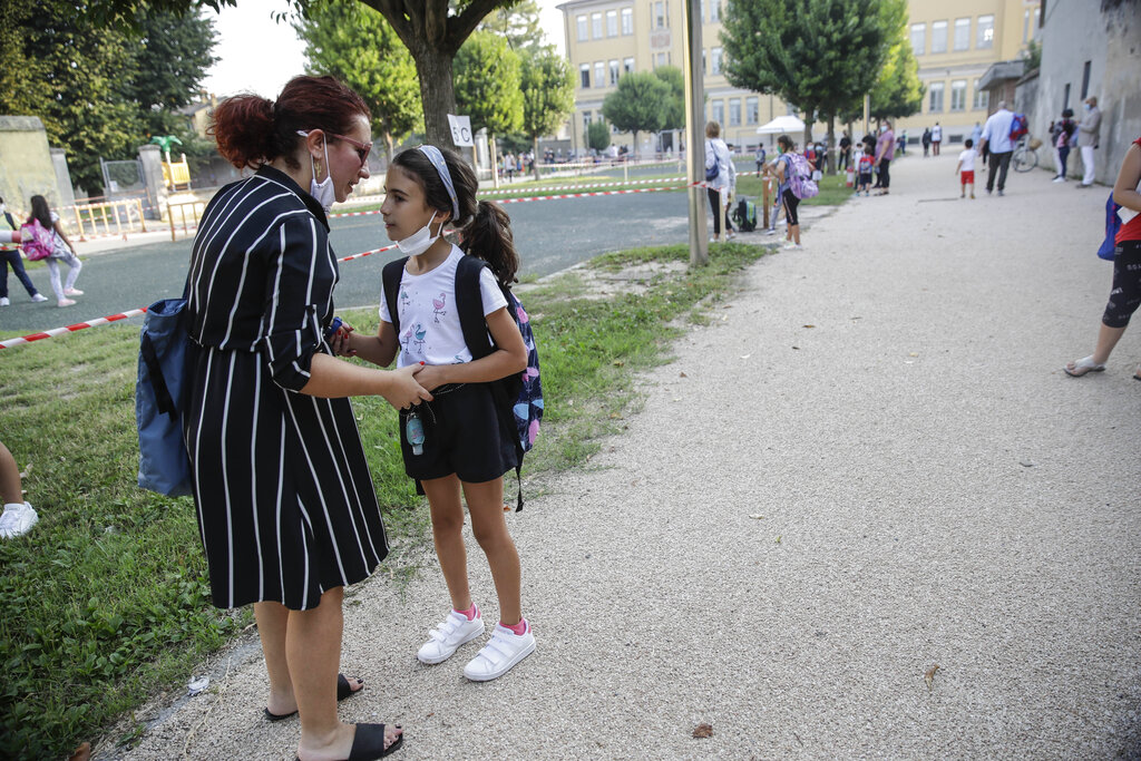 Maria Cristina Baggi greets her ten-year-old daughter Cecilia Rungi outside the San Biagio primary school in Codogno, Italy, Monday, Sept. 14, 2020. The morning bell Monday marks the first entrance to the classroom for the children of Codogno since Feb. 21,  when panicked parents were sent to pick up their children after the northern Italian town gained notoriety as the first in the West to record local transmission of the coronavirus. (AP Photo/Luca Bruno)
