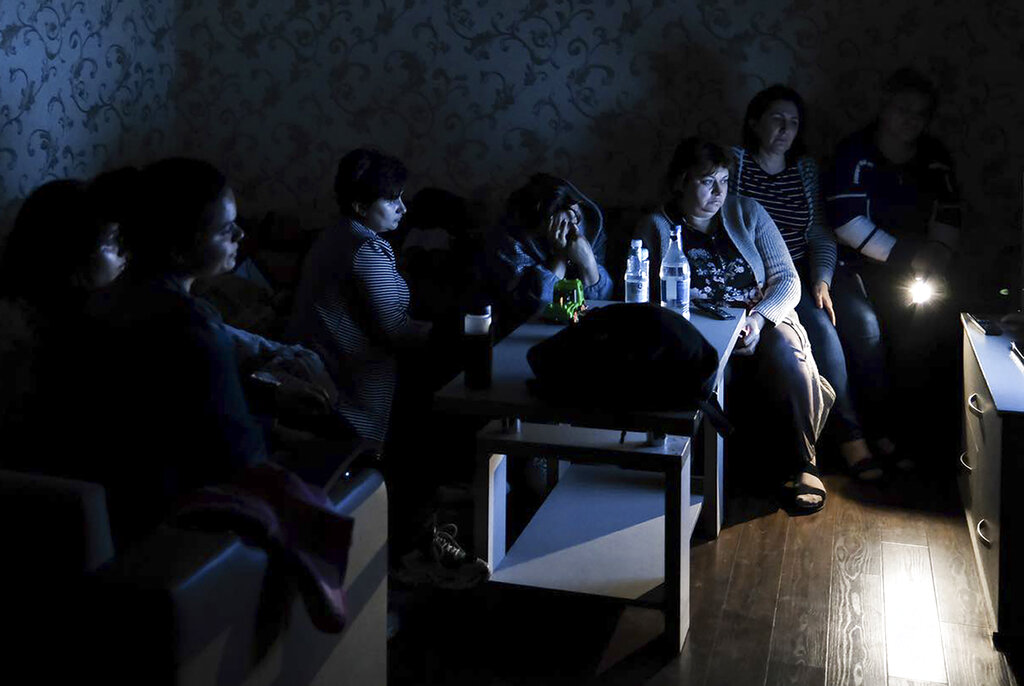 In this handout photo released by the Armenian Foreign Ministry on Monday, Sept. 28, 2020, people watch the State TV as they gather in a bomb shelter to protect against the shelling in Stepanakert, the self-proclaimed Republic of Nagorno-Karabakh, Azerbaijan. Nagorno-Karabakh authorities reported that shelling hit the region's capital of Stepanakert and the towns of Martakert and Martuni. Armenian Defense Ministry spokesman Artsrun Hovhannisyan also said Azerbaijani shelling hit within Armenian territory near the town of Vardenis. (Armenian Foreign Ministry via AP)