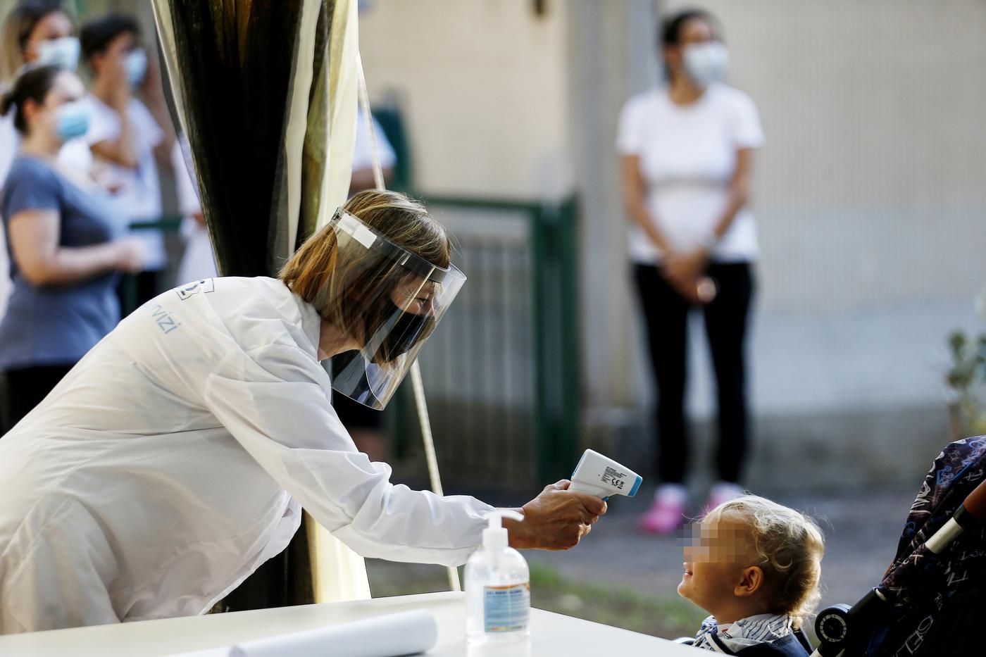 A un bambino viene misurata la temperatura all'entrata a scuola (Cecilia Fabiano/ LaPresse)