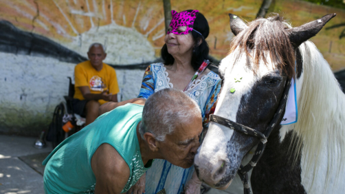 An elderly person kisses a horse named Tony at the