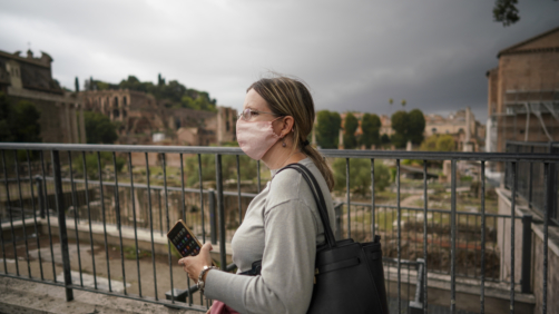 A woman wears a face mask to prevent the spread of COVID-19 as she walks by the ancient Roman Forum, in downtown Rome, Saturday, Oct. 3, 2020. As of Saturday it is mandatory to wear masks outdoors in Lazio, the region that includes Rome. (AP Photo/Andrew Medichini)