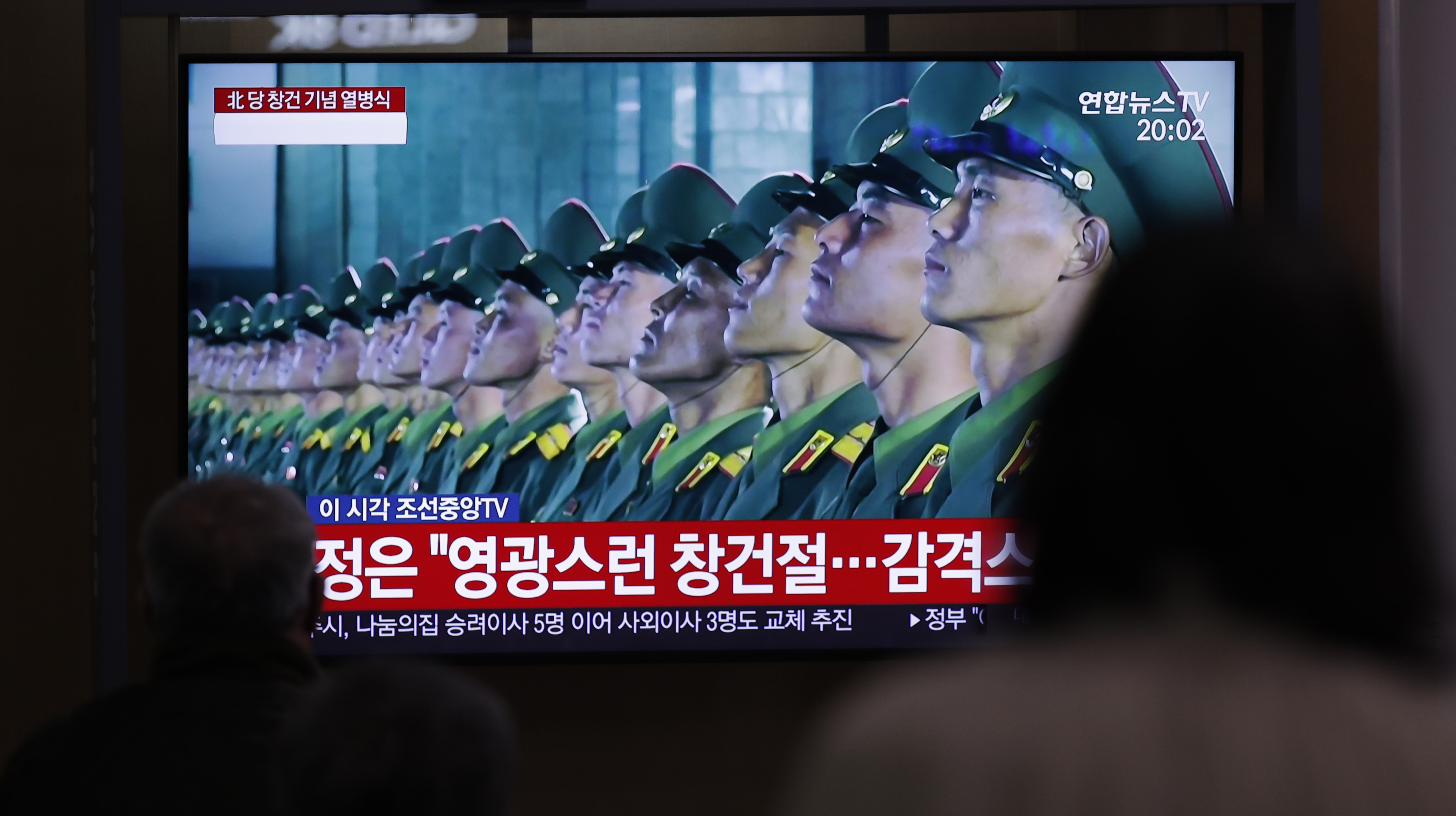 People wearing face masks watch a TV screen during a news program reporting about the ceremony to mark the 75th founding anniversary of the North Korea's ruling Workers' party, at the Seoul Railway Station in Seoul, South Korea, Saturday, Oct. 10, 2020. A part of letters read on the top