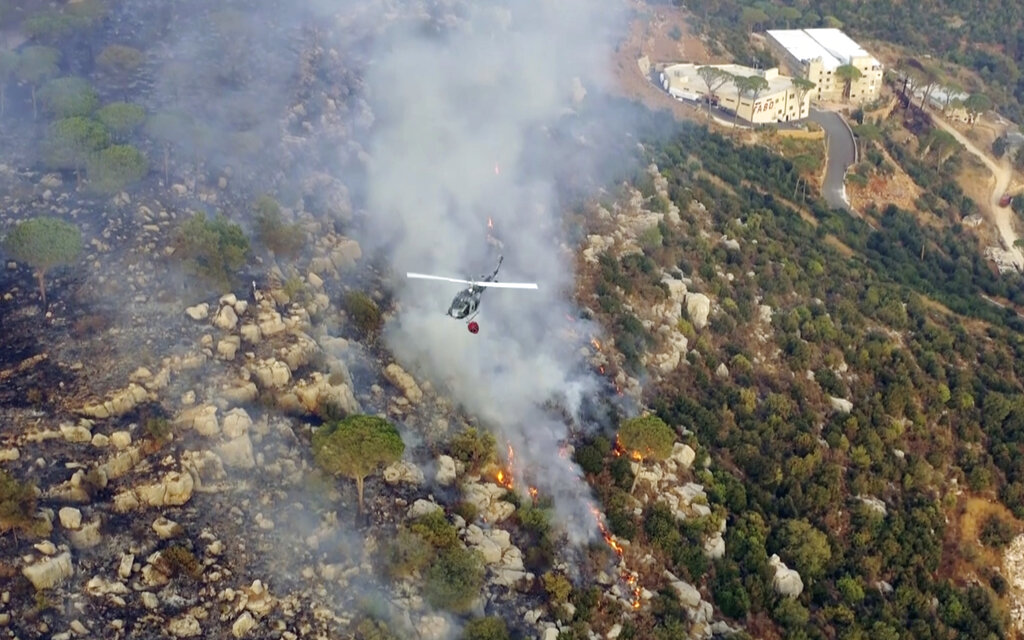 In this frame grab from video, an army helicopter drops water on a fire at the scene of forest fire in Ras el-Harf village, in the Baabda district, Lebanon, Friday, Oct. 9, 2020. Wildfires around the Middle East triggered by a heatwave hitting the region have killed two people, forced thousands of people to leave their homes and detonated landmines along the Lebanon-Israel border, state media and officials said Saturday. (AP Photo)