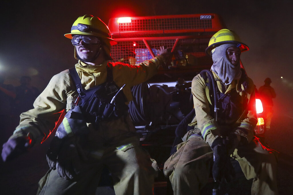 Firefighters sit on a vehicle amid fires in Cordoba, Argentina, late Monday, Oct. 12, 2020. Wildfires have destroyed thousands of hectares in the Argentine province of Cordoba this year, amid a drought and high temperatures. (AP Photo/Nicolas Aguilera)
