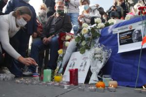 Una donna accende una candela nella manifestazione a Parigi, 18 ottobre (AP Photo/Michel Euler)