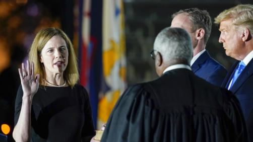 President Donald Trump watches as Supreme Court Justice Clarence Thomas administers the Constitutional Oath to Amy Coney Barrett on the South Lawn of the White House White House in Washington, Monday, Oct. 26, 2020, after Barrett was confirmed to be a Supreme Court justice by the Senate earlier in the evening. Holding the Bible is Barrett's husband, Jesse Barrett. (AP Photo/Patrick Semansky)
