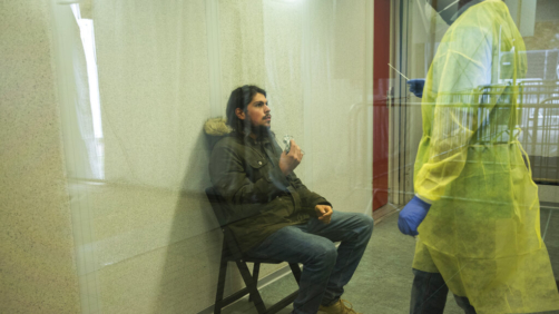 "A medical worker, wearing full protective gear, talks to a patient as he takes a nose swab to be tested for COVID-19 in a Red Cross test center in Brussels, Tuesday, Oct. 20, 2020. Bars and restaurants across Belgium shut down for a month and a night-time curfew entered into force Monday in the hard-hit coronavirus country as health authorities warned of a possible sanitary ""tsunami."