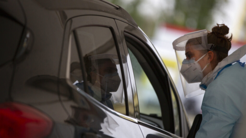 A health care worker speaks with a man in a car as she prepares to administer a nose-swab test at the mobile COVID-19 testing site in Antwerp, Belgium, Tuesday, Oct. 20, 2020. Bars and restaurants across Belgium have been shut down for a month and a night-time curfew entered into force Monday, as health authorities warned of a possible sanitary