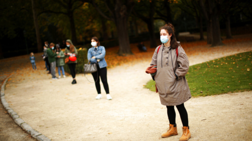 People, wearing masks and keeping social distance to prevent the spread of the coronavirus, wait in line to be tested in a Red Cross COVID-19 test center at Cinquantenaire park in Brussels, Monday, Oct. 19, 2020. Bars and restaurants across Belgium shut down for a month and a night-time curfew entered into force Monday in the hard-hit coronavirus country as health authorities warned of a possible sanitary