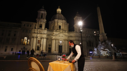 A waiter clears a table at a cafe restaurant in Piazza Navona Square before the start of a curfew, Friday, Oct. 23, 2020. In much of Europe, city squares and streets, be they wide, elegant boulevards like in Paris or cobblestoned alleys in Rome, serve as animated evening extensions of drawing rooms and living rooms. As Coronavirus restrictions once again put limitations on how we live and socialize, AP photographers across Europe delivered a snapshot of how Friday evening, the gateway to the weekend, looks and feels. (AP Photo/Alessandra Tarantino)