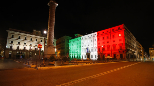Palazzo Chigi Government office is lit with the color of the Italian flag, early Monday, Oct. 26, 2020. Since an 11 p.m.-5 a.m. curfew took effect Friday, people can only move around during those hours for reasons of work, health or necessity. (AP Photo/Alessandra Tarantino)