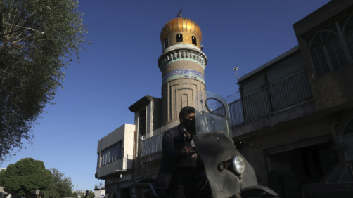 A man drives past a mosque during the Muslim holy fasting month of Ramadan, in southern Tehran, Iran, Monday, April 27, 2020. In Iran, the country that is hit worst in the Middle East by the coronavirus, all religious gathering, congregational prayers and communal Iftar servings, a meal eaten at sunset to break the fast, remain forbidden in the Ramadan and also holy shrines and religious centers also continue to be closed until at least May 4. (AP Photo/Vahid Salemi)