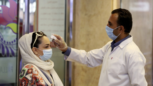 A woman wearing a protective face mask to help prevent spread of the coronavirus has her temperature checked as she enters a shopping center, in Tehran, Iran, Wednesday, Aug. 19, 2020. Iran surpassed 20,000 confirmed deaths from the coronavirus on Wednesday, the health ministry said — the highest death toll for any Middle East country so far in the pandemic. (AP Photo/Ebrahim Noroozi)
