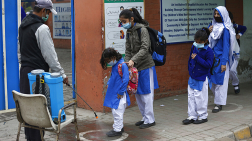 A worker sprays sanitizer on the shoes of students as they arrive at a school in Lahore, Pakistan, Wednesday, Nov. 25, 2020. Pakistan will again close all educational institutions as of Thursday Nov. 26, 2020, because of a steady and increasingly drastic increase in coronavirus cases. (AP Photo/K.M.Chaudary)