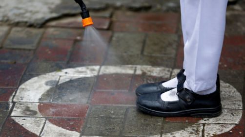 A worker sprays sanitizer on a student's shoes at a school in Lahore, Pakistan, Wednesday, Nov. 25, 2020. Pakistan will again close all educational institutions as of Thursday Nov. 26 because of a steady and increasingly drastic increase in coronavirus cases. (AP Photo/K.M.Chaudary)