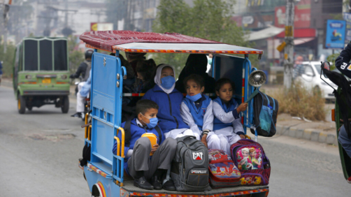 Students wearing face masks to protect against the coronavirus, ride in a tri-wheeler to school in Lahore, Pakistan, Wednesday, Nov. 25, 2020. Pakistan will again close all educational institutions as of Thursday Nov. 26, 2020, because of a steady and increasingly drastic increase in coronavirus cases. (AP Photo/K.M.Chaudary)
