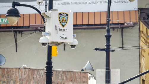 FILE - This photo from Friday Aug. 19, 2016, shows police surveillance cameras, top, on a light post overlooking the area of the Masjid At-Taqwa mosque at Bedford and Fulton Streets in Brooklyn, N.Y. Amnesty International is calling on New York City and state officials to ban law enforcement from using facial recognition technology, saying it threatens the civil rights of