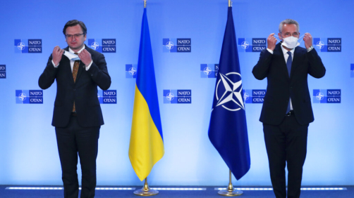 NATO Secretary General Jens Stoltenberg, right, and Ukraine's Foreign Minister Dmytro Kuleba take off their protective face masks prior to an official greeting at NATO headquarters in Brussels, Tuesday, April 13, 2021. (AP Photo/Francisco Seco, Pool)