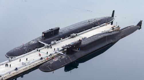 In this handout photo released by Russian Defense Ministry Press Service, Russian nuclear submarines Prince Vladimir, above, and Yekaterinburg stay berthside at a Russian naval base in Gazhiyevo, Kola Peninsula, Russia, Russia, Tuesday, April 13, 2021.  Russian Defense Minister Sergei Shoigu on Tuesday described a massive military buildup in western Russia as part of drills intended to check the armed forces' readiness amid the threats posed by NATO. (Vadim Savitsky/Russian Defense Ministry Press Service via AP)