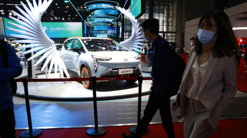 Attendees pass by a vehicle from the GAC Group displayed during the Shanghai Auto Show in Shanghai on Monday, April 19, 2021. Automakers are looking to China, their biggest market by sales volume and the first major economy to rebound from the pandemic, to revive sales and reverse multibillion-dollar losses. (AP Photo/Ng Han Guan)
