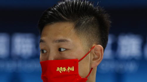 A promoter for the Chinese luxury auto brand Hongqi wears a mask that reads