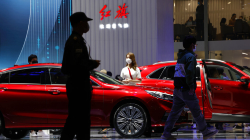 A promoter for Chinese luxury auto brand Hongqi waits for visitors near the brand's latest cars at the Shanghai Auto Show in Shanghai on Tuesday, April 20, 2021. Automakers are looking to China, the biggest auto market by sales volume and the first major economy to rebound from the pandemic, to propel a revival in demand and reverse multibillion-dollar losses. (AP Photo/Ng Han Guan)