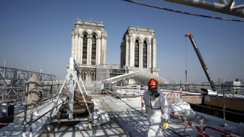 A worker is pictured at the reconstruction site of the Notre-Dame cathedral, Thursday, April 15, 2021 in Paris. Two years after a fire tore through Paris' most famous cathedral and shocked the world, French President Emmanuel Macron is visiting the building site that Notre Dame has become Thursday to show that French heritage has not been forgotten despite the coronavirus. (Benoit Tessier/Pool via AP)