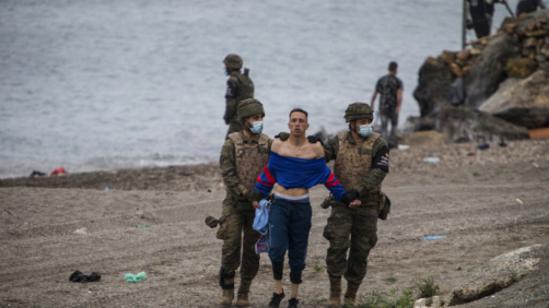 A man from Morocco is detained by soldiers of the Spanish Army at the border of Morocco and Spain, at the Spanish enclave of Ceuta, on Tuesday, May 18, 2021. Ceuta, a Spanish city of 85,000 in northern Africa, faces a humanitarian crisis after thousands of Moroccans took advantage of relaxed border control in their country to swim or paddle in inflatable boats into European soil. Around 6,000 people had crossed by Tuesday morning since the first arrivals began in the early hours of Monday, including 1,500 who are presumed to be teenagers. (AP Photo/Javier Fergo)