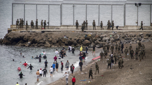Spanish Army take positions as people from Morocco arrive in the Spanish territory next to the border of Morocco and Spain, at the Spanish enclave of Ceuta, on Tuesday, May 18, 2021. Ceuta, a Spanish city of 85,000 in northern Africa, faces a humanitarian crisis after thousands of Moroccans took advantage of relaxed border control in their country to swim or paddle in inflatable boats into European soil. Around 6,000 people had crossed by Tuesday morning since the first arrivals began in the early hours of Monday, including 1,500 who are presumed to be teenagers. (AP Photo/Javier Fergo)