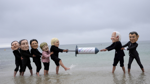 Activists wearing giant heads of the G7 leaders tussle over a giant COVID-19 vaccine syringe during an action of NGO's on Swanpool Beach in Falmouth, Cornwall, England, Friday, June 11, 2021. Leaders of the G7 begin their first of three days of meetings on Friday in Carbis Bay, in which they will discuss COVID-19, climate, foreign policy and the economy. Depicted from left to right, Japan's Prime Minister Yoshihide Suga, Italy's Prime Minister Mario Draghi, Canadian Prime Minister Justin Trudeau, German Chancellor Angela Merkel, British Prime Minister Boris Johnson, U.S. President Joe Biden and French President Emmanuel Macron. (AP Photo/Kirsty Wigglesworth)