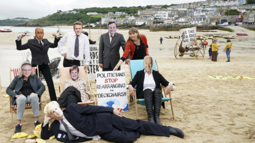 Activists pose with faces of the G7 and other world leaders as they demonstrate on the beach in the harbour near the G7 meeting taking place in St. Ives, Cornwall, England, Friday, June 11, 2021. Leaders of the G7 begin their first of three days of meetings on Friday in Carbis Bay, in which they will discuss COVID-19, climate, foreign policy and the economy. Leaders faces from left, Australia's Prime Minister Scott Morrison, Russian President Vladimir Putin, British Prime Minister Boris Johnson, French President Emmanuel Macron, German Chancellor Angela Merkel, Italy's Prime Minister Mario Draghi and U.S. President Joe Biden. (AP Photo/Jon Super)
