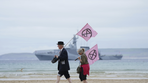 Two protestors holds flags as they walk on the beach of Carbis Bay during a demonstration outside the G7 meeting taking place in St. Ives, Cornwall, England, Friday, June 11, 2021. Leaders of the G7 begin their first of three days of meetings on Friday in Carbis Bay, in which they will discuss COVID-19, climate, foreign policy and the economy. (AP Photo/Jon Super)