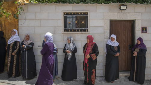 Palestinian women wait by the family house to take the last look at the body of Ahmad Shamsa, 15, during his funeral in the West Bank village of Beta, near Nablus, Thursday, June. 17, 2021. The Palestinian health ministry said Thursday that Shamsa who was shot by Israeli troops in the West Bank a day earlier died of his injuries. (AP Photo/Nasser Nasser)