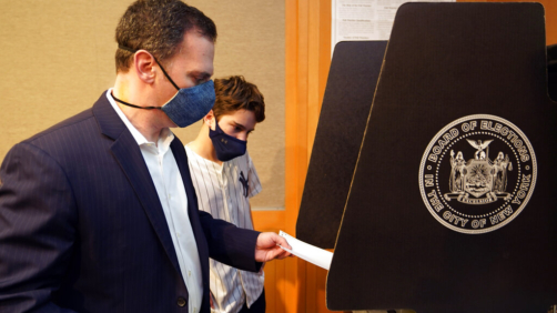 New York State Assembly member, and candidate for Manhattan district attorney, Dan Quart, with his son Sam, enters his ballot at an early voting site at the Metropolitan Museum of Art, in New York, Thursday, June 17, 2021. (AP Photo/Richard Drew)