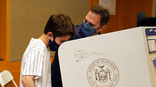New York State Assembly member, and candidate for Manhattan district attorney, Dan Quart, with his son Sam, marks his ballot at an early voting site at the Metropolitan Museum of Art, in New York, Thursday, June 17, 2021. (AP Photo/Richard Drew)